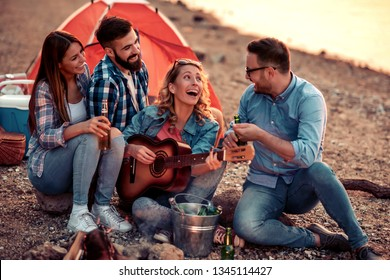 Camp on the beach.Group of young friends having picnic on the beach at night.