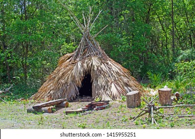 Camp setting of Seminole or Caribe Indian tiki hut tent made of palm fronds tied together with sticks and vines sitting behind a log bench and fire pit, and branch fences with green wooded background.