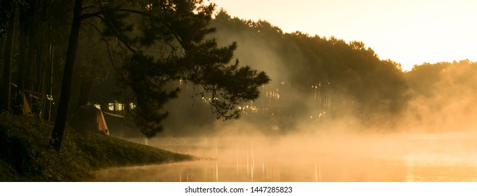Camp site in national park in forest with lake in morning beautiful view of fog on surface water, dimension for banner