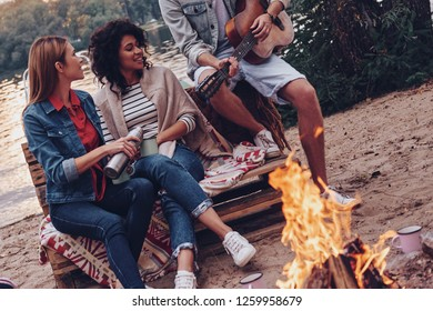 Camp songs. Group of young people in casual wear smiling while enjoying beach party near the campfire