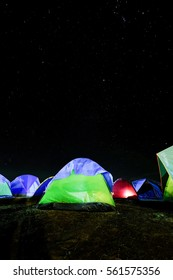 Camp tent under a night sky with full of stars.