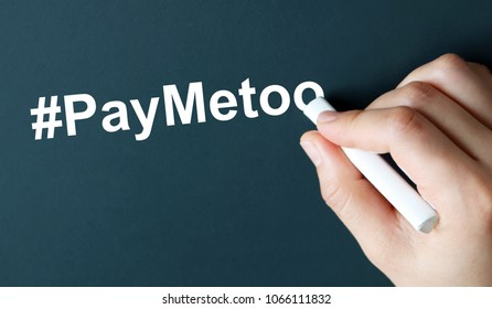 Thehandwritingtext#PayMeTooinwhitechalk. A campaign to close the gender pay gap.