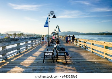 "Campbell River, Canada - June 23, 2017: People enjoying the view form the Fishing Pier. at Sunset. Campbell River has long been touted as ""the Salmon Capital of the World""."