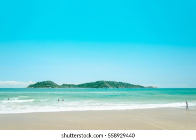 Campeche beach: People playing on the beach with a green water and an island on the background on a beautiful sunny day landscape.