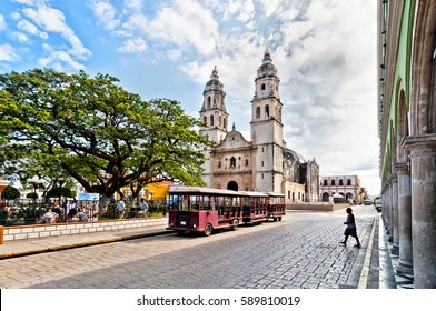 Campeche, Mexico - April 19, 2014: locals and tourists in main square with Cathedral in Campeche, Mexico. The city was founded in 1540 by Spanish conquistadores atop pre-existing Maya city