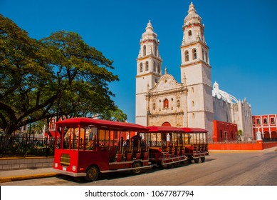 Campeche, Mexico: Independence Plaza, tourist trains and cathedral on the opposite side of the square. Old Town of San Francisco de Campeche