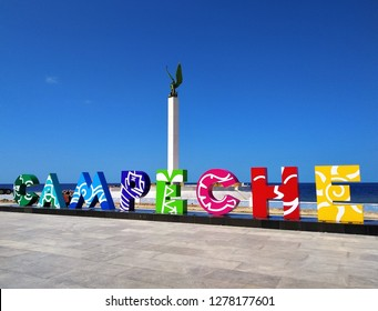 CAMPECHE, MEXICO - JANUARY 2019: View of colorful sign Campeche with statue and sea in background on Malecon in center of Campeche, beautiful historic colonial city in Yucatan, Mexico on sunny day.