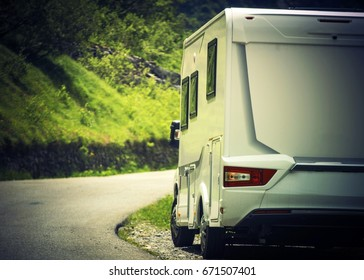 Camper Camping Vacation. Motorhome on the Side of the Scenic Mountain Road.