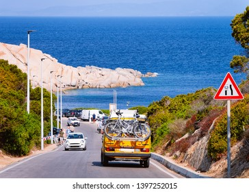 Camper car with bicycles driving in the highway road at Capo Testa in Santa Teresa Gallura at the Mediterranean Sea on Sardinia Island in Summer Italy. Holiday adventure in mountains.