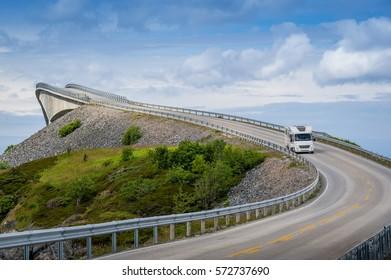 Camper car is driving on the curved bridge on Atlantic Ocean Road, Norway.