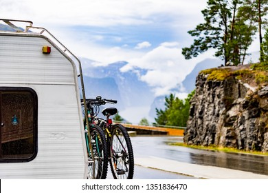 Camper car motorhome with bicycles on roadside in mountains, Aurland fjord and Stegastein viewpoint in distance. Camping on trip. National tourist route Aurlandsfjellet Norway.
