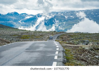 Camper car in norwegian mountains. Tourism vacation and travel. Caravan car RV travels on the mountain road, pass Norway. Scandinavia Europe. Norwegian national tourist scenic route.