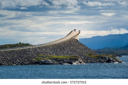 Camper car on the famous Atlantic Ocean Road bridge, which has a visual effect of a cliff. National travel route of Norway, road 64.