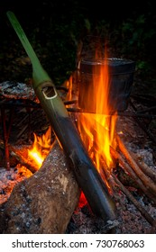 camper fire cooking by field pot and boil water by green bamboo pipe