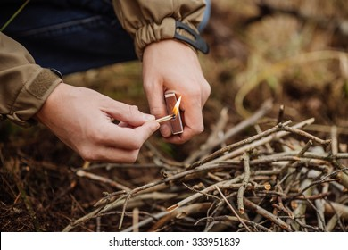 camper holds a lit match under the kindling to start a camp fire