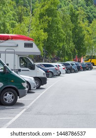 Camper motor home with canoe on top roof and cars on rest stop location, parking area. Travel, active lifestyle concept.