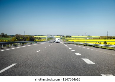 Camper RV van driving fast on French highway toward holiday destination and clear blue sky