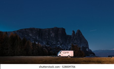 Camper RV van at rock and night star sky background. Dolomites mountains, Italy. Night scene with camper van.