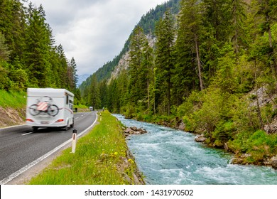 Camper van with attached bicycle driving through the European Alps on a rainy day.