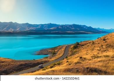 Camper van driving an empty road on the Pukaki lake - New Zealand