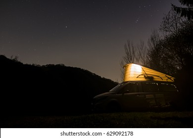 Camper van with lift-up elavating roof in starry sky night