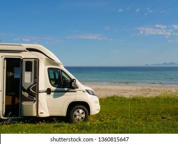 Camper van motor home on sea coast Gimsoysand beach in summer. Camping on ocean shore. Lofoten archipelago Norway. Vacation and travel in caravan.