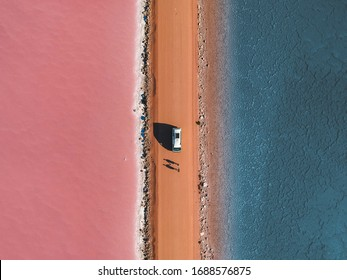 A camper van parked in the middle of one of the most beautiful pink and blue lakes - Lake Macdonnell, South Australia. Two people are standing in front of the camper van.