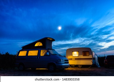 A camper van with its pop top roof open parked next to a vintage caravan in a campsite at nightfall, both illuminated from inside and the moon glowing above in a stormy sky.