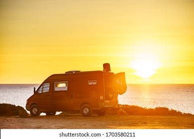 Camper van recreational vehicle at sunrise on mediterranean coast in Spain. Camping on nature beach. Vacation and traveling in motor home.