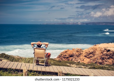 Camper watching the waves of portugal in a chair
