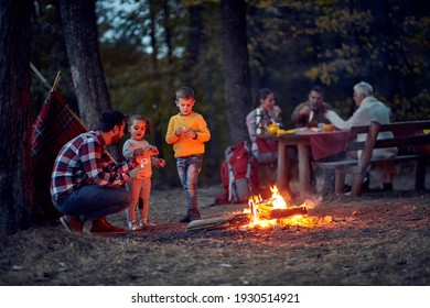 Campers with children enjoying in wood near campfire