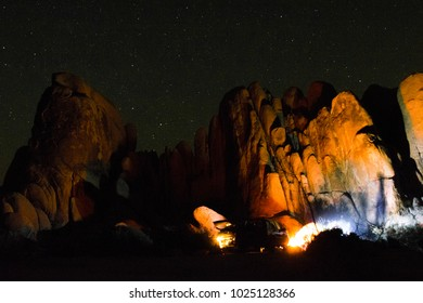 Campers in Joshua Tree National Park illuminating rocks with campfire.