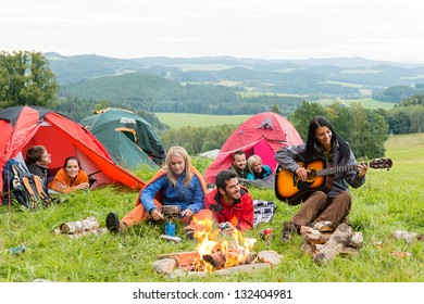 Campers in tents listening to girl playing guitar beside campfire