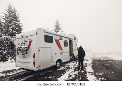 campervan caravan vehicle for van life holiday on camper van journey camping in winter mountains near the forest snowing on the camper outdoor nomad lifestyle with dog