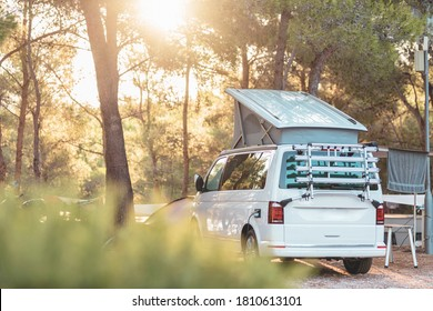 Campervan caravan vehicle for van life holiday on mobile home camper mobile motor home. Golden sunshine sneaking through sparse trees of camping. Roof of campervan is covered in colourful sunshine