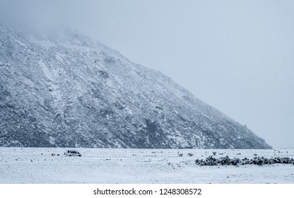 A campervan driving on the road in a snowy day. Mount Cook Village valley.