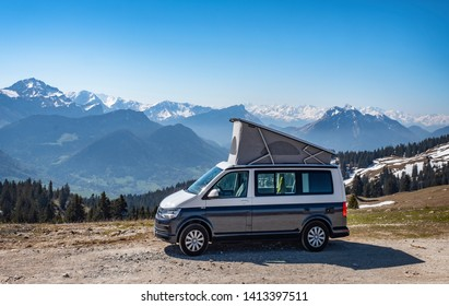 Campervan in Jura, French Alps - May 10, 2019: camping with small lifting roof van in snow covered mountains of France.