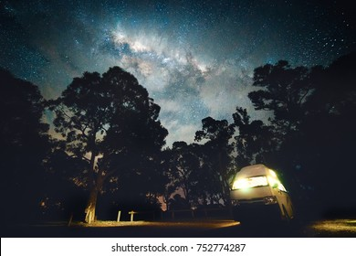 Campervan with the milky way in a forest.