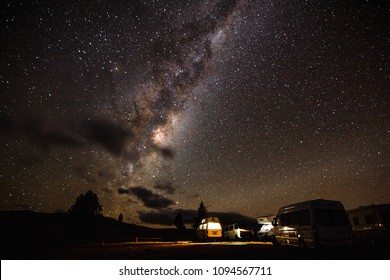 Campervans parked below the Milky Way in New Zealand