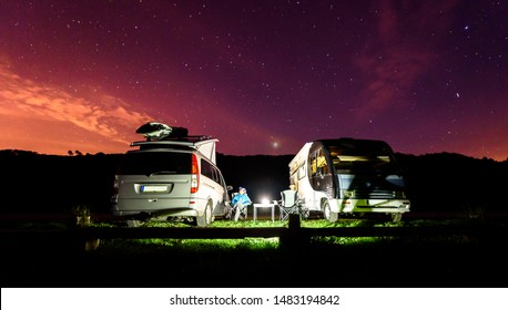 Campervans are parked on a beach at night under stars. A man camping with two camping vans is enjoying the evening relaxation under thew starry night in Soesto beach - Galicia, Spain.