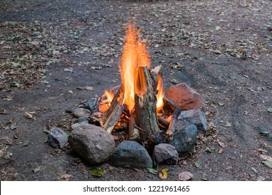 Campfire ablaze with stone circle at daylight with earth background