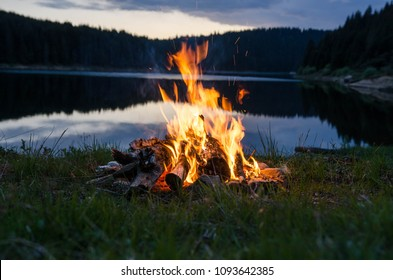 Campfire after sunset in the mountains - in the background lake and forest