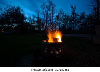 A campfire in the back yard at night with tall trees in the background under dark blue sky