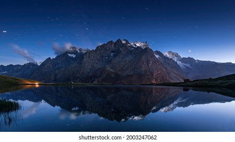 Campfire and bivouac under the stars in front of Ecrins National Park massif with La Meije peak. Lac du Pontet in Hautes-Alpes. Oisans Massif (French Alps). France - Shutterstock ID 2003247062