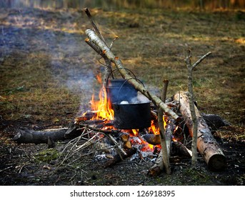 campfire with black iron pan with soup