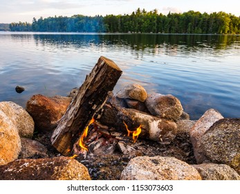 A campfire burning in a stone fire ring along the shore of a river in Maine.