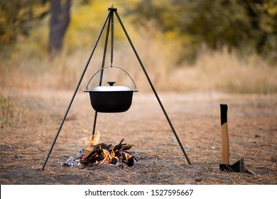 Campfire with camping tools such as axe and hanging pot over fire. Secluded relaxation in autumn forest away from bustle of city