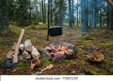 Campfire with camping tools such as axe, kåsa and hanging pot over fire.