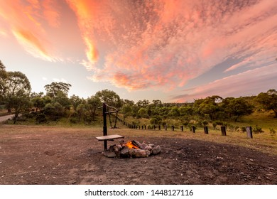Campfire with fire burning in a campground in the Australian outback and a beautiful sunset sky overhead.