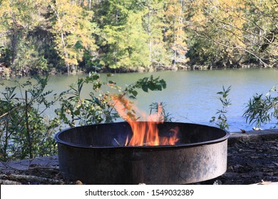 Campfire in fire ring at campsite beside the river .